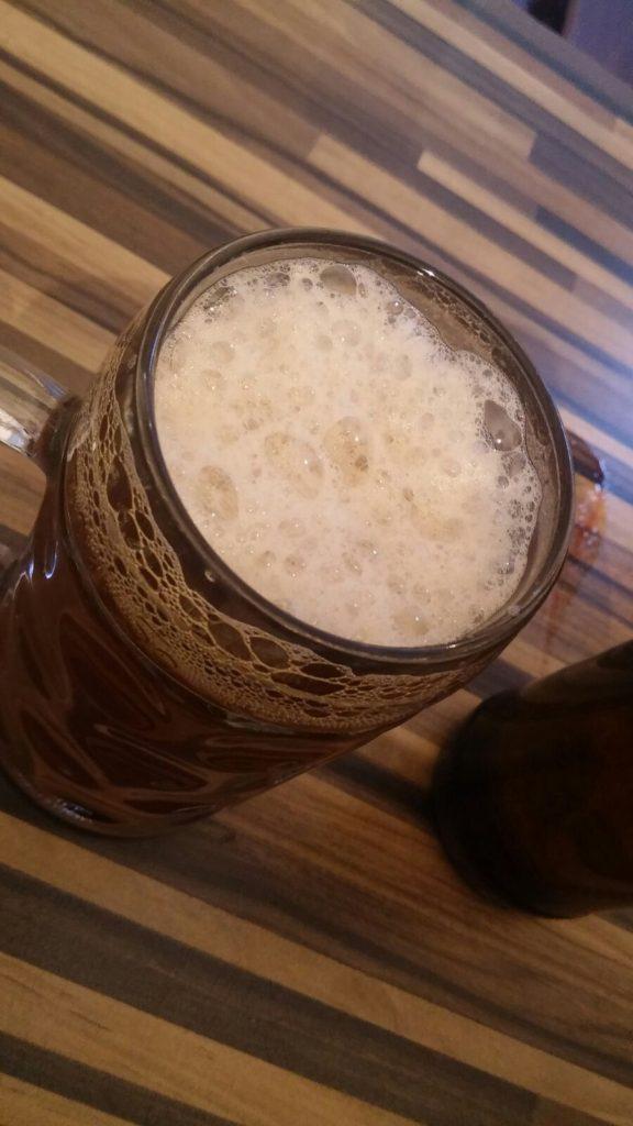 Das welovebier.de- Team zeigt ein Bild, auf dem das selbstgebraute Bier in einen Bierkrug auf einem Tisch steht und die Schaumkrone gut zu sehen ist.