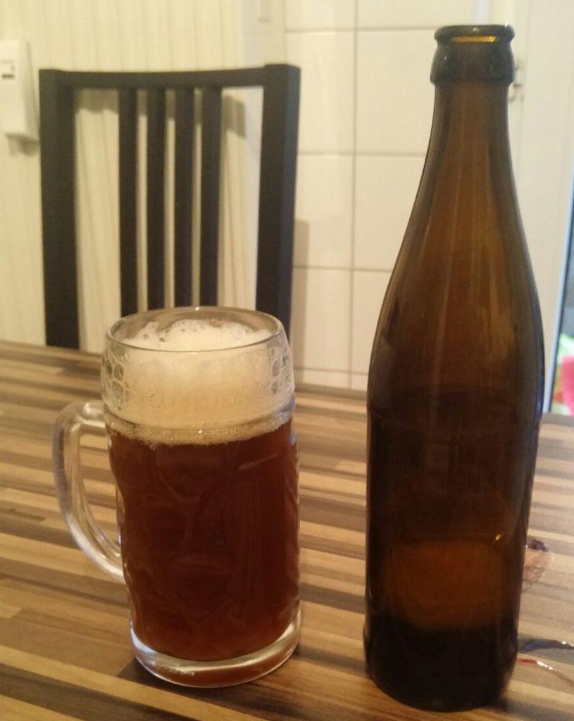 Das welovebier.de- Team zeigt ein Bild, auf dem das selbstgebraute Bier in einen Bierkrug und daneben die leere Bierflasche auf einem Tisch steht.