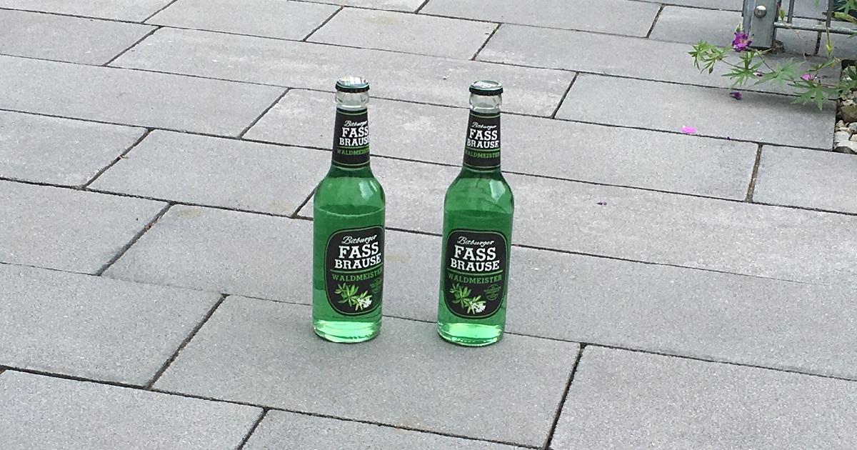 Auf einem Steinboden stehen zwei Flaschen von der Bitburger Fassbrause in der Geschmacksrichtung Waldmeister.
