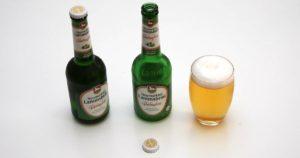 Das welovebier.de- Team zeigt ein Bild, auf dem zwei Flaschen glutenfreies Bier der Marke Neumarkter Lammsbräu zu sehen sind. Daneben ist ein volles Glas Bier mit dem Bierdeckel zu sehen,