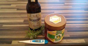 Passend zu dem Beitrag, ob warmes Bier bei einer Erkältung hilft ist ein Bier mit einem Glas Honig und einem Fieberthermometer zu sehen.
